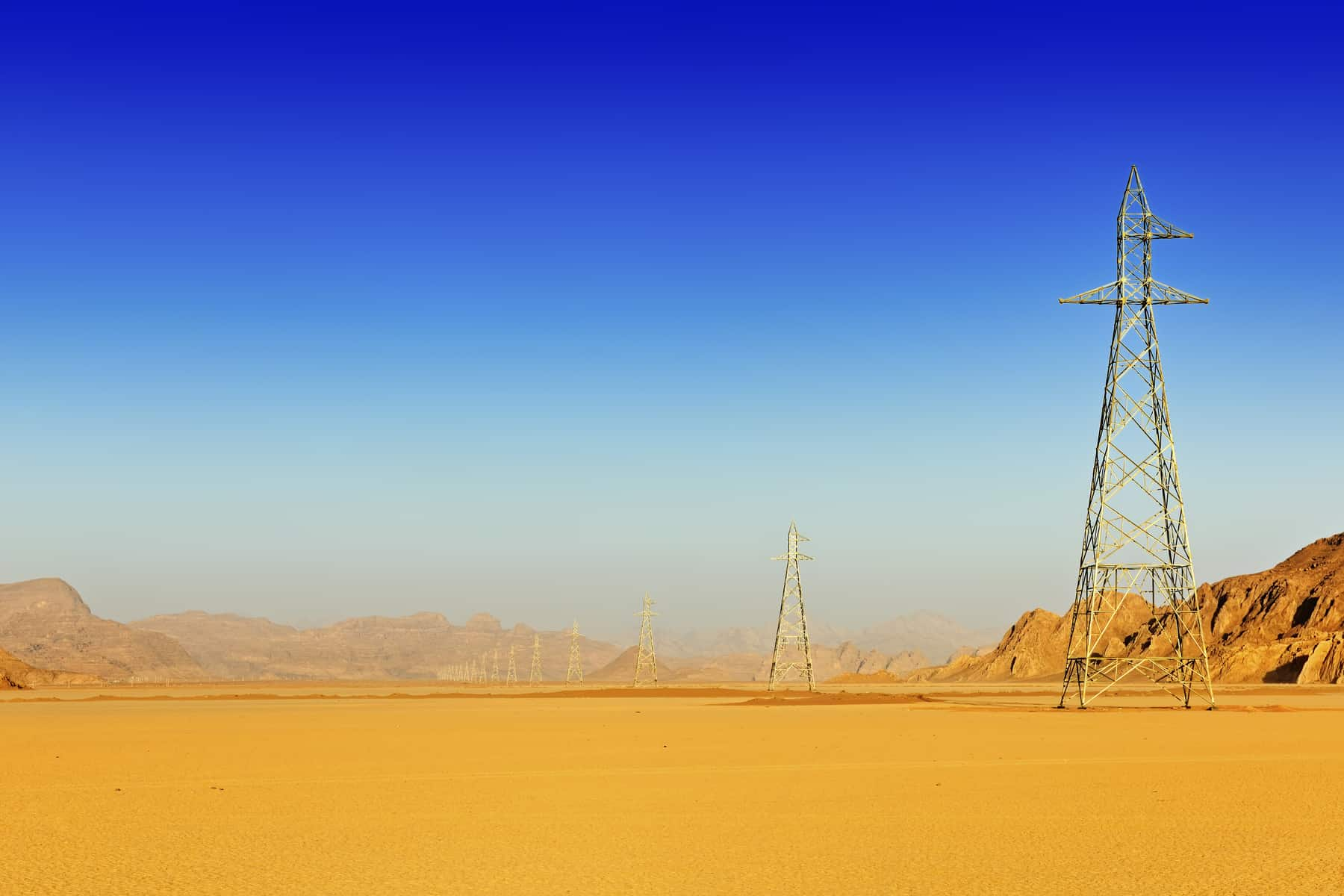 Row of high voltage pylons in the desert of Wadi Rum, Jordan, Middle East ©Pierre Brumder | Adobe Stock Photo